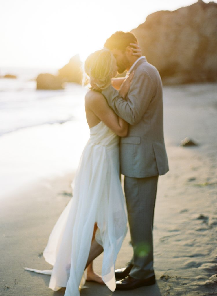 Couple embracing on the beach photographed by wedding photographer Catherine of Peony Park Photography in southern California