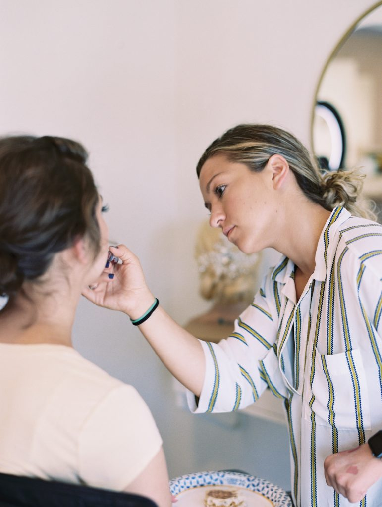 Behind the scenes wedding photograph of bride getting hair and makeup taken by Catherine, a wedding photographer in southern california