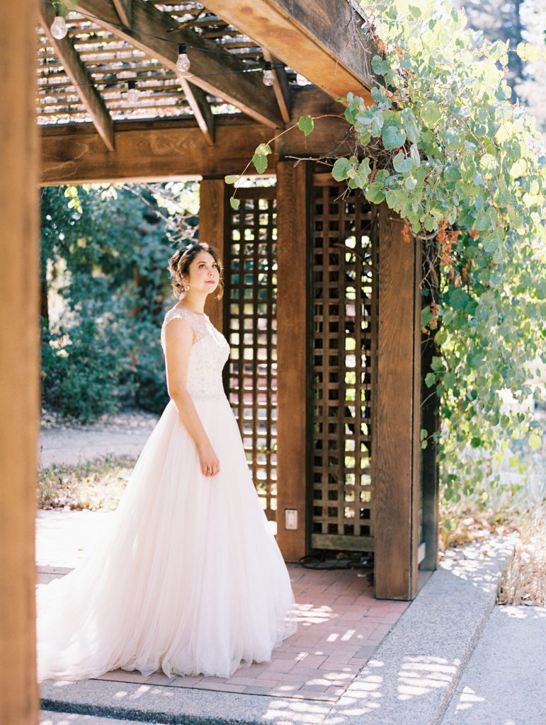 Bride entering a garded with a wooden entrance taken by wedding photographer Catherine of by Peony Park Photography out of Souther California