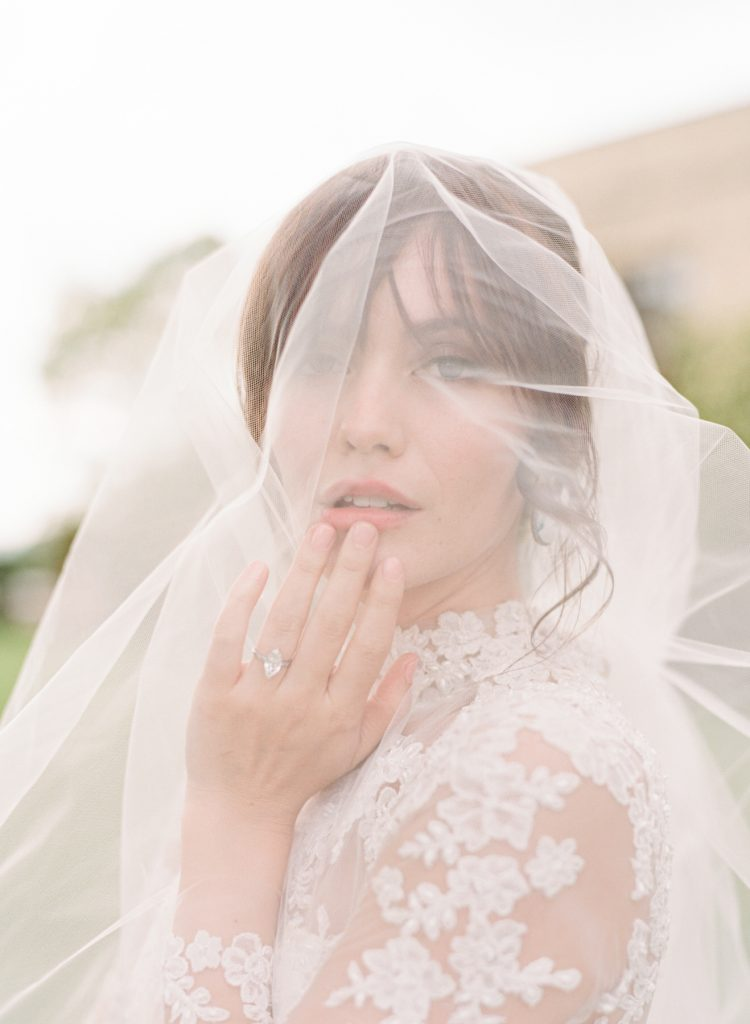 Bride in lacy wedding gown and veil touching her lips at Hedsor House Shot by Fine Art Photographer Catherine of Peony Park Photography
